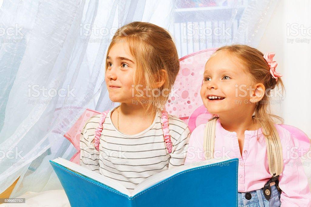 Little beautiful pixies reading the fairy-tale stock photo