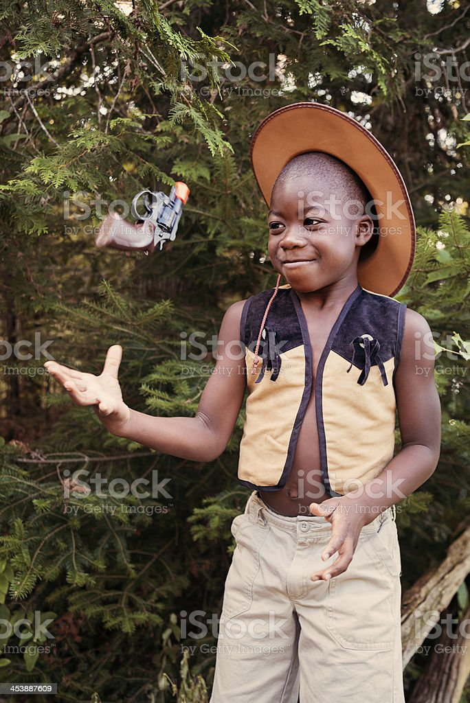 Little black boy playing cowboy with a toy gun. royalty-free stock photo