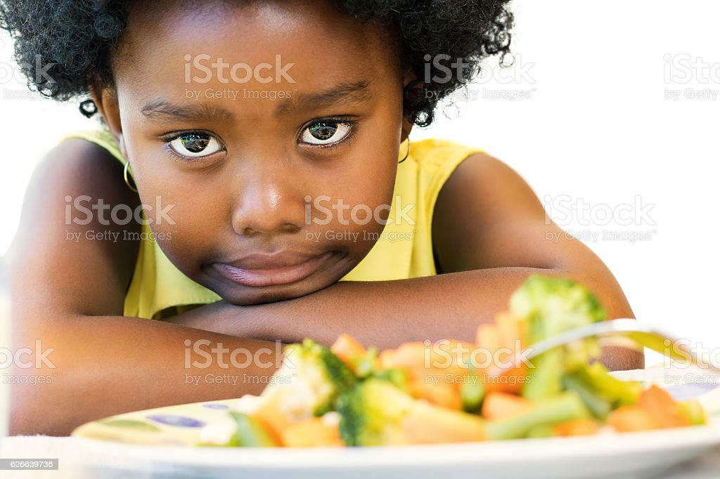 Little black girl pulling up nose for vegetables. stock photo