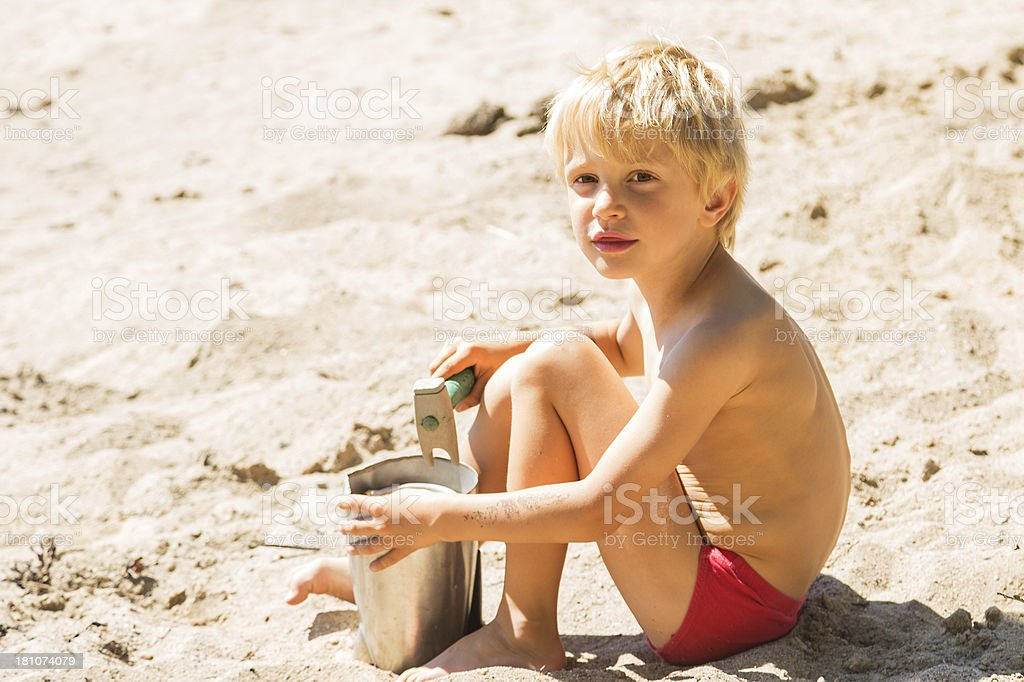 Little blond boy playing in the sand royalty-free stock photo