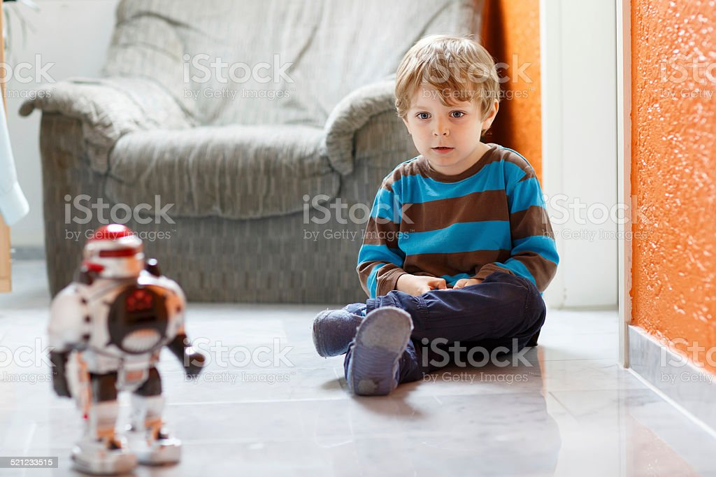 Little blond boy playing with robot toy at home, indoor. stock photo