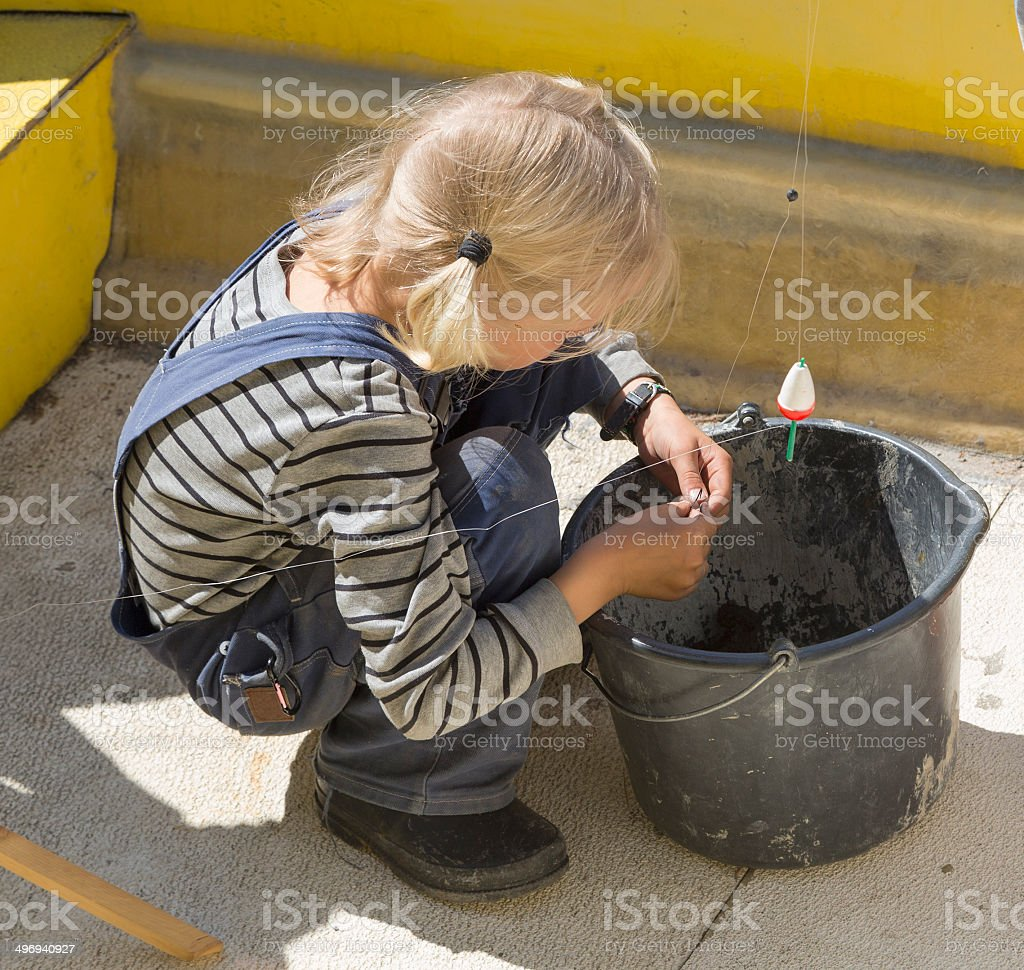 Little blond boy putting a worm on the hook. royalty-free stock photo