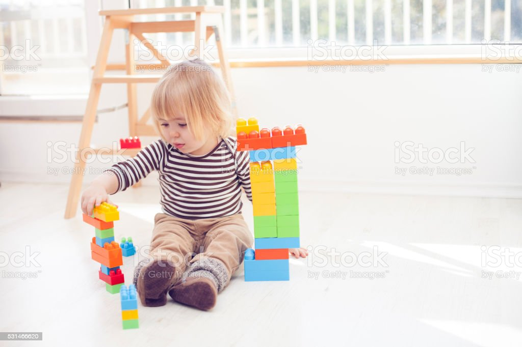 Little blond child playing with colorful plastic blocks stock photo