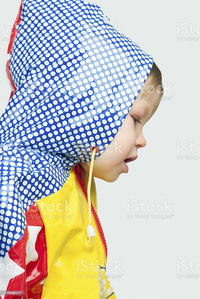 Little blond girl in raincoat stock photo