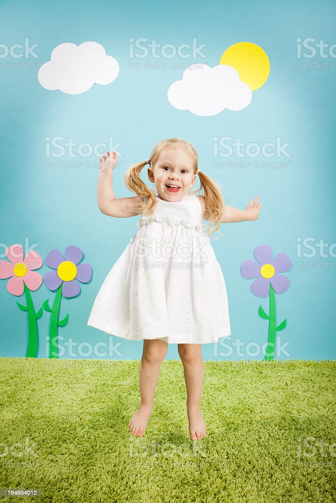 Little Blond Girl Smiling and Jumping in Whimsical Outdoor World stock photo