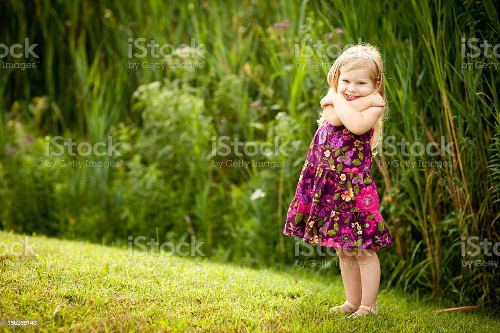Little Blond Girl, With Beautiful Smile, Giving Herself Hug stock photo