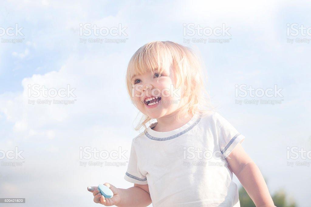 Little blonde boy and sidewalk chalks stock photo