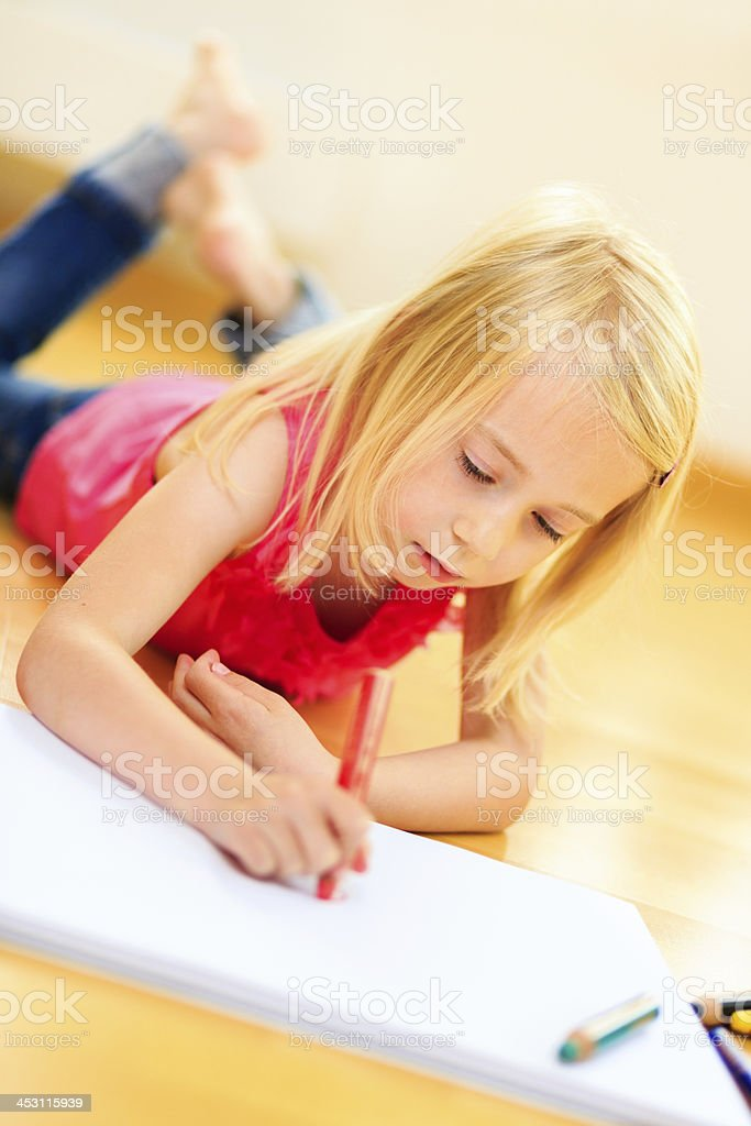 Little blonde girl drawing in living room royalty-free stock photo