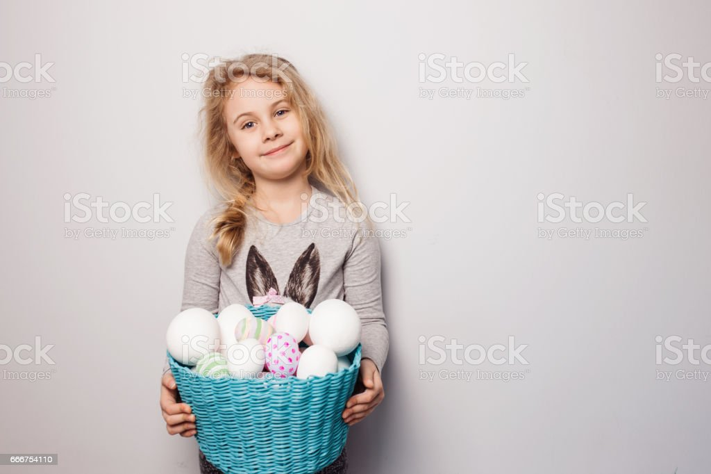 Little blonde girl holding basket with painted eggs. Easter day. stock photo