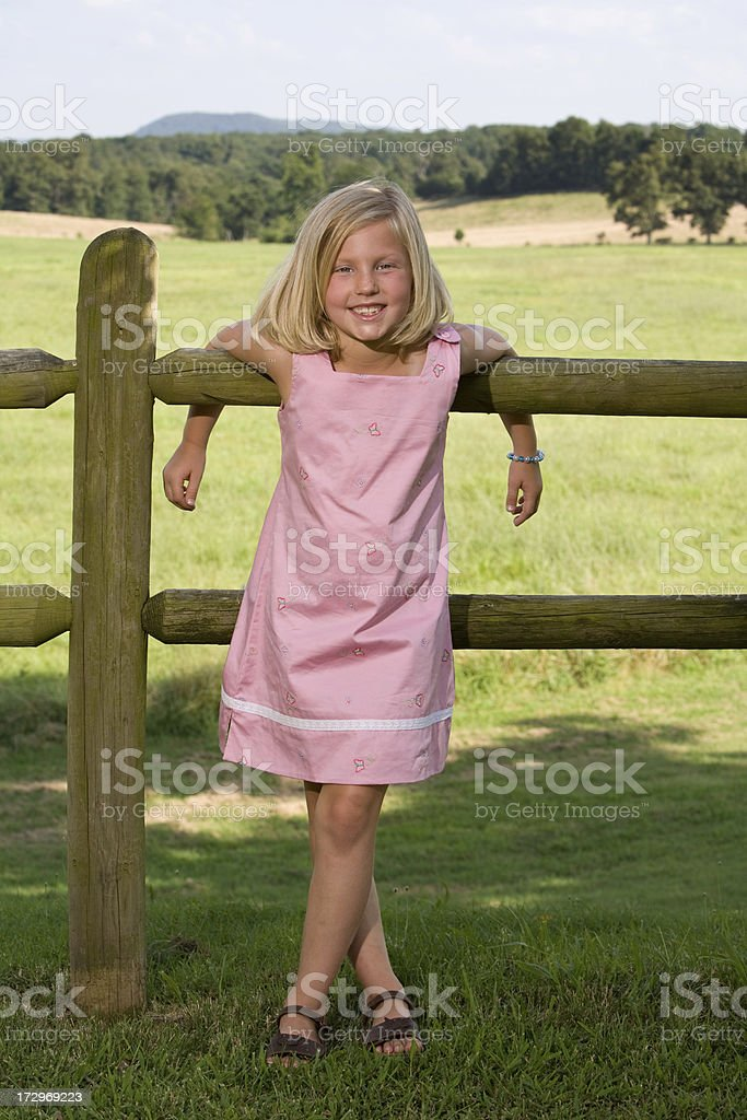 little blonde girl in front of fence royalty-free stock photo