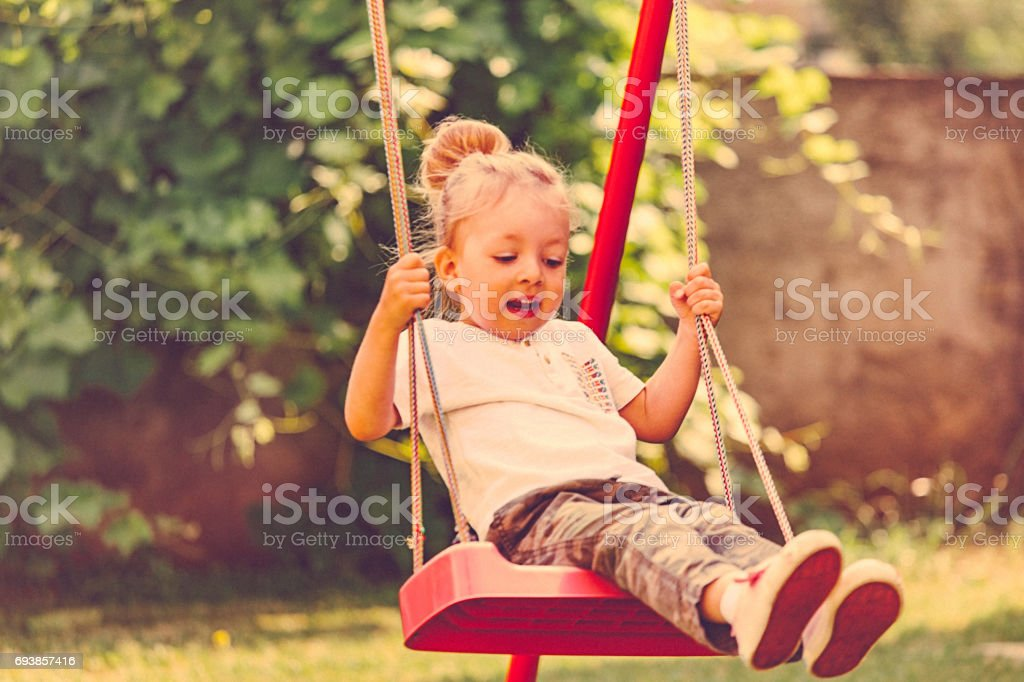 Little blonde girl playing on swing stock photo