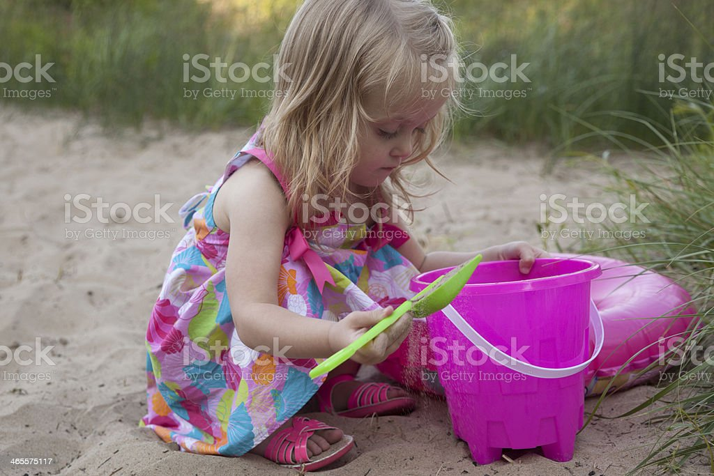 Little Blonde Girl playing with Pink Bucket on Sandy Beach royalty-free stock photo