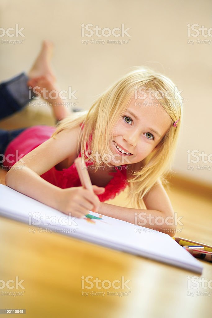 Little blonde girl smiling at camera while drawing royalty-free stock photo
