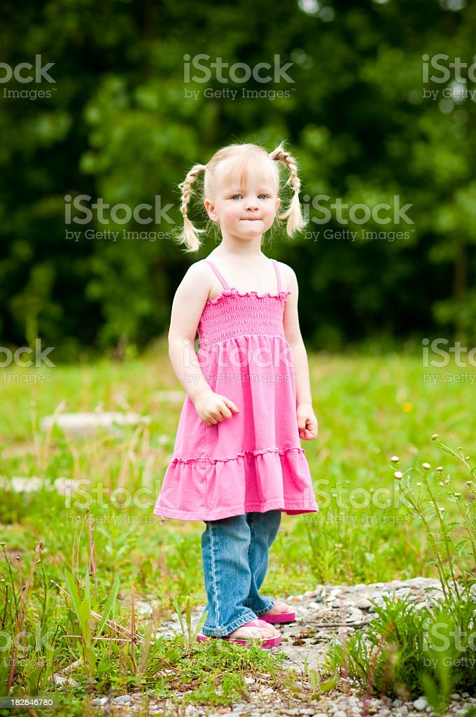 Little Blonde Girl Standing in Field Outside royalty-free stock photo