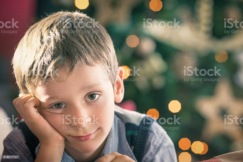 Little blonde smiling boy in front of a christmas tree stock photo