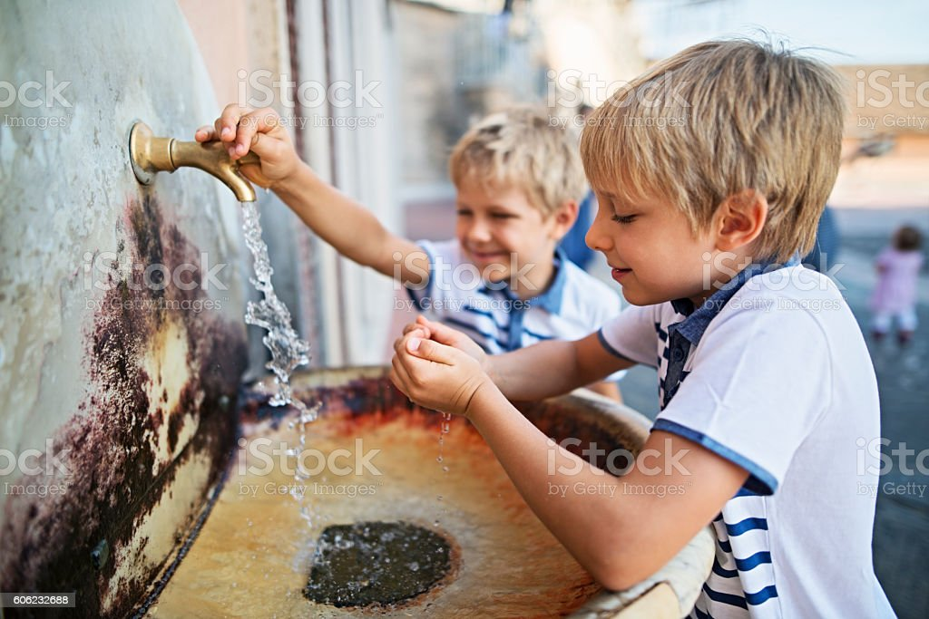 Little bosy drinking tap water from publish sink stock photo