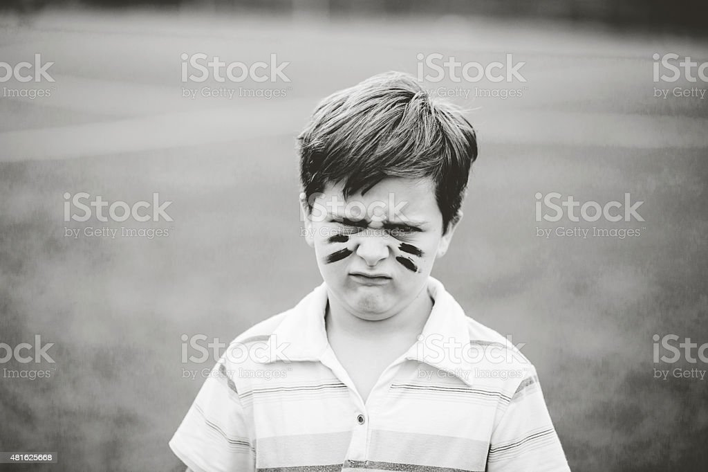 Little boy acting angry in a park. Making silly faces. stock photo