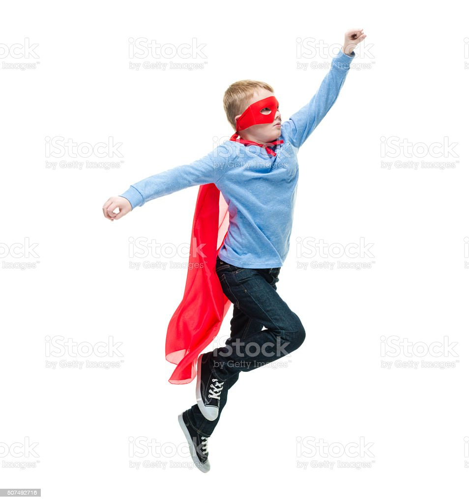 Little boy acting like superman and flying stock photo