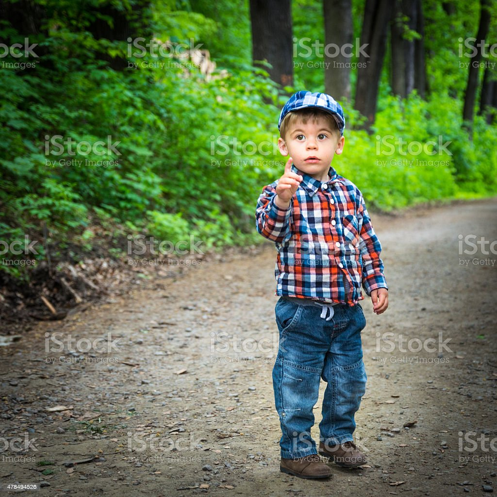 Little boy alone in a park stock photo