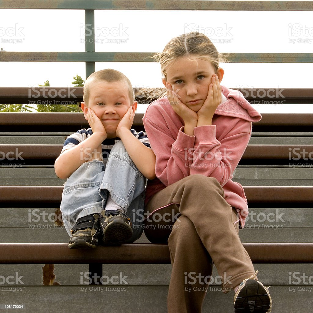 Little Boy and Bored Young Girl Sitting on Bleachers royalty-free stock photo