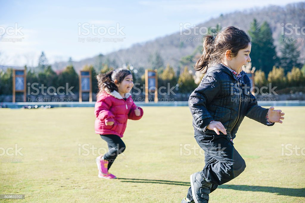 Little boy and girl, brother and sister, plays at lawn stock photo