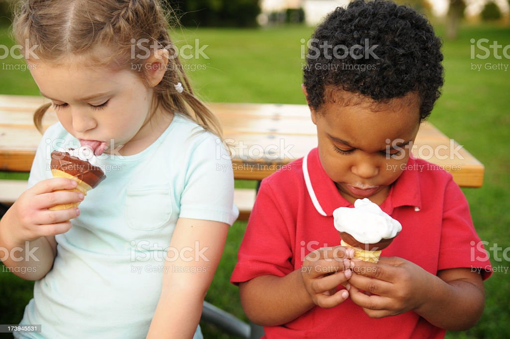 Little Boy and Girl Eating Ice Cream Cones Outside royalty-free stock photo