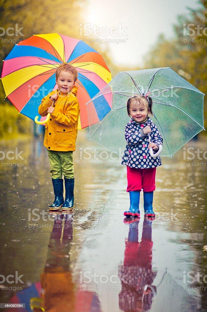 Little boy and girl in rain stock photo