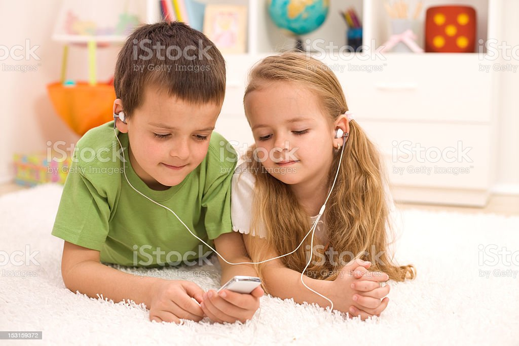 Little boy and girl listening to music stock photo