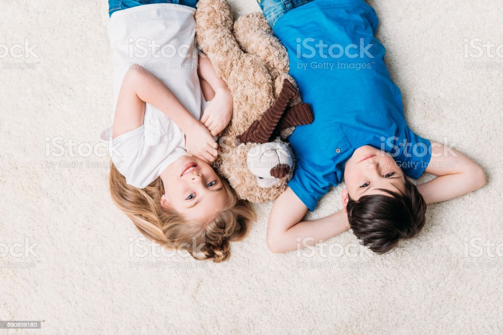 little boy and girl lying on carpet with teddy bear at home and looking at camera stock photo