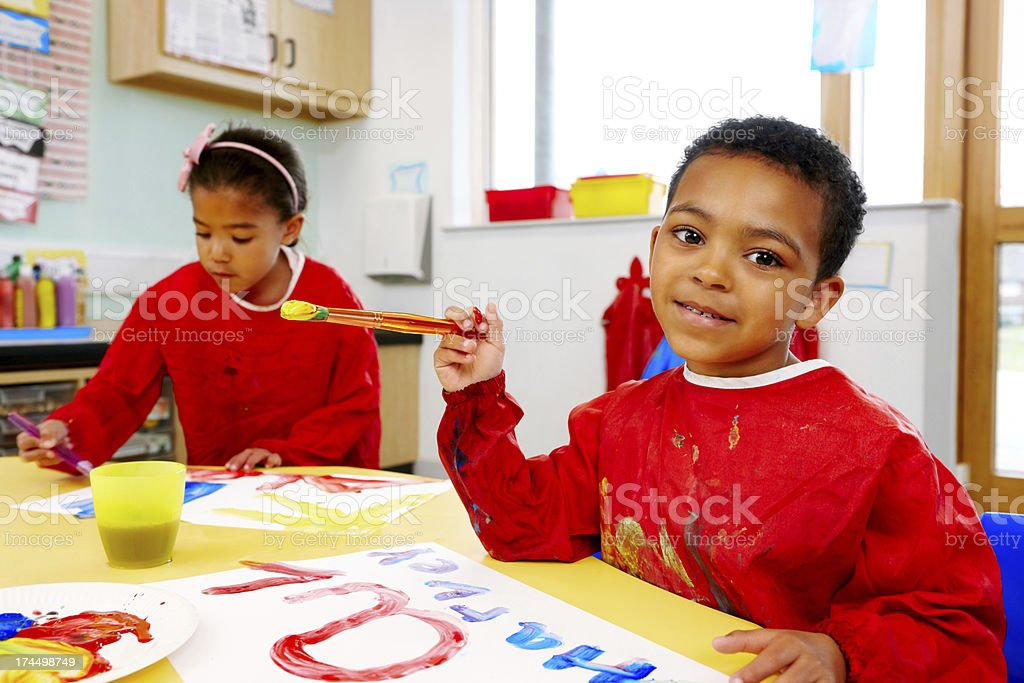 Little boy and girl painting in playschool royalty-free stock photo