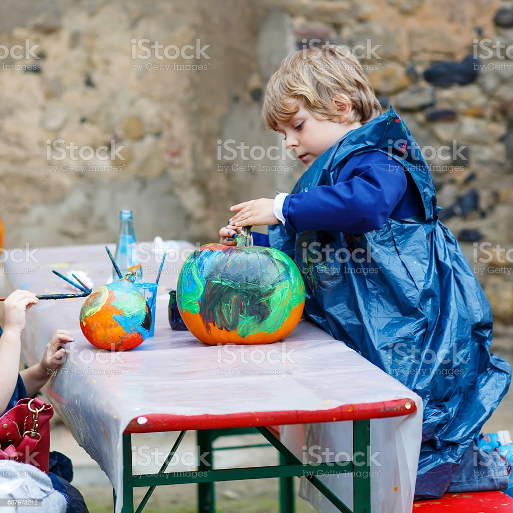 Little boy and girl painting with colors on pumpkin stock photo