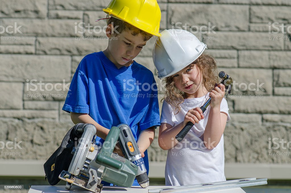 Little boy and girl playing with big tools outside stock photo