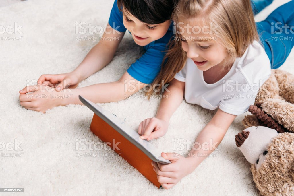 little boy and girl playing with digital tablet while lying on carpet at home stock photo