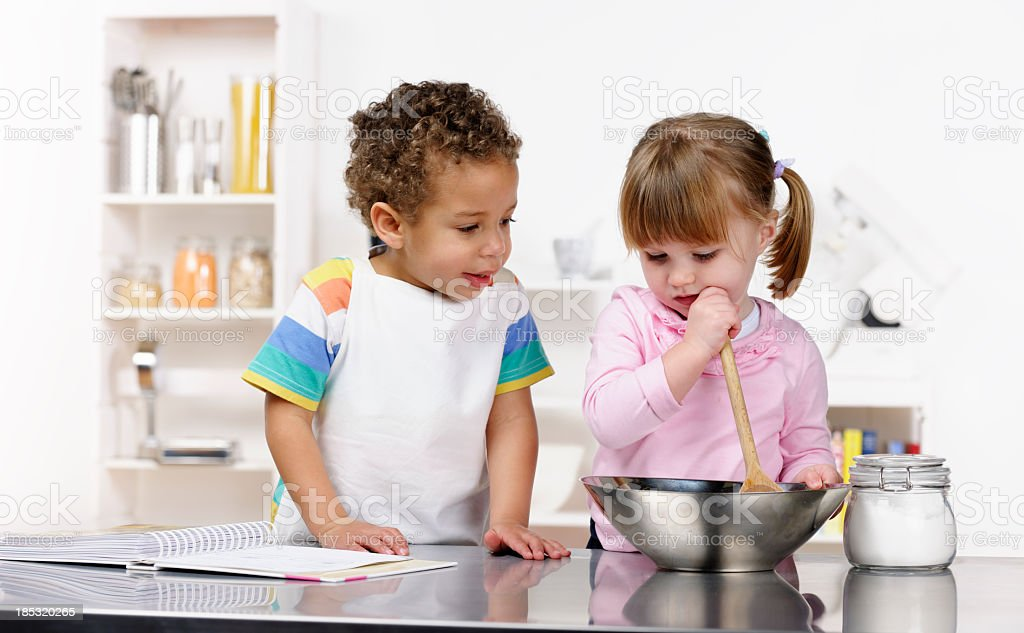 Little Boy And Girl Preparing Food In The Kitchen stock photo