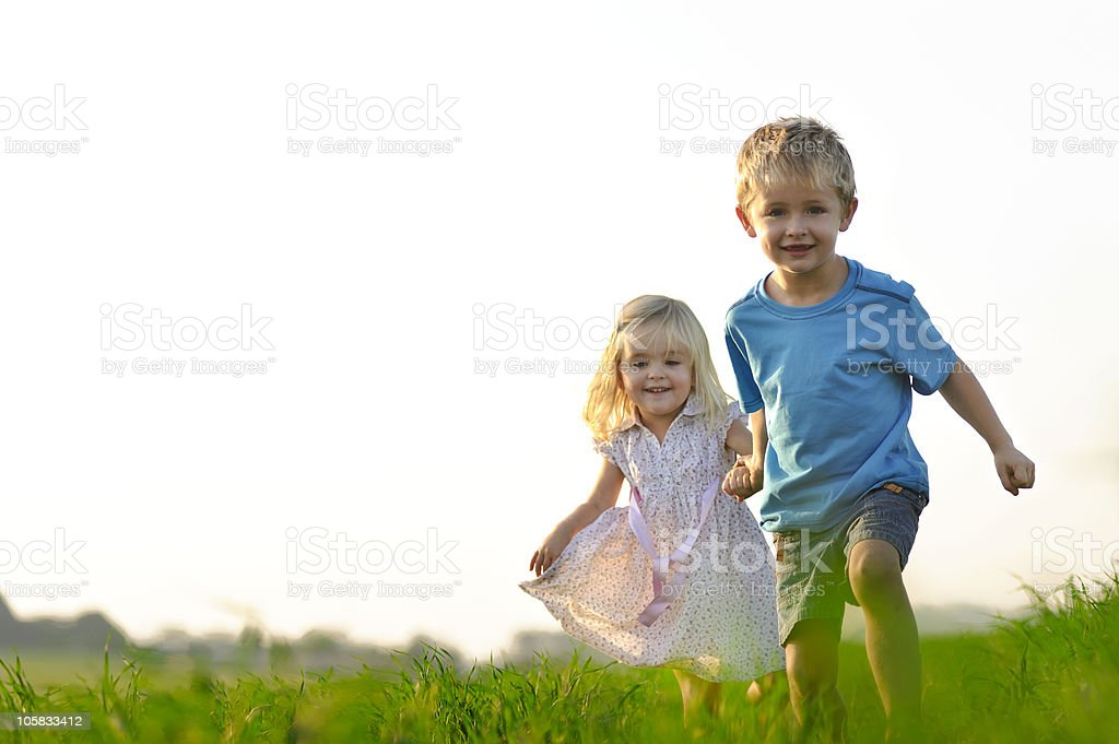 Little boy and girl running through the grass smiling stock photo