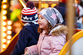 little boy and girl, siblings on carousel at Christmas market