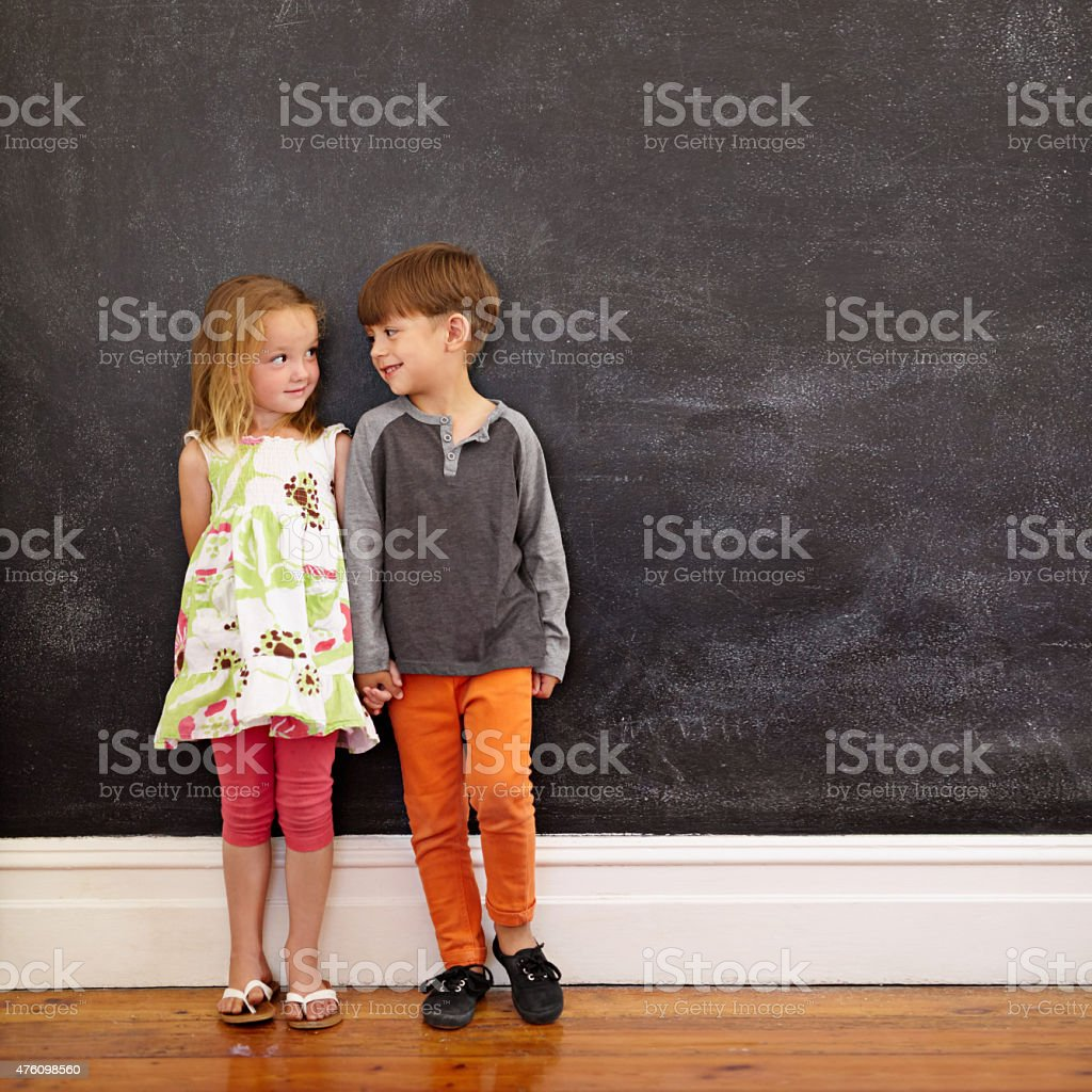 Little boy and girl standing in front of blackboard stock photo