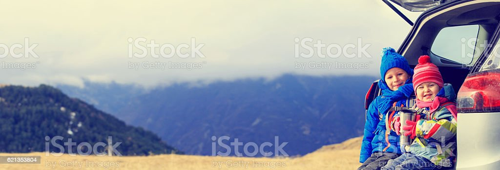 little boy and girl travel by car in mountains, panorama stock photo