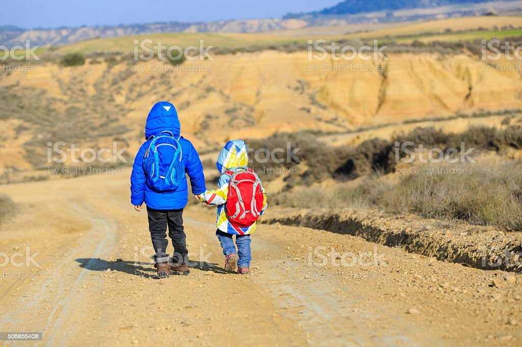 little boy and girl travel on the road to mountains stock photo