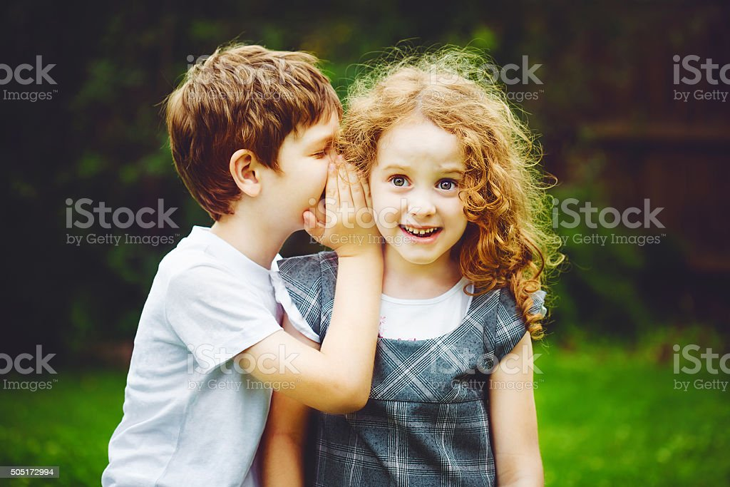 Little boy and girl whispers. stock photo