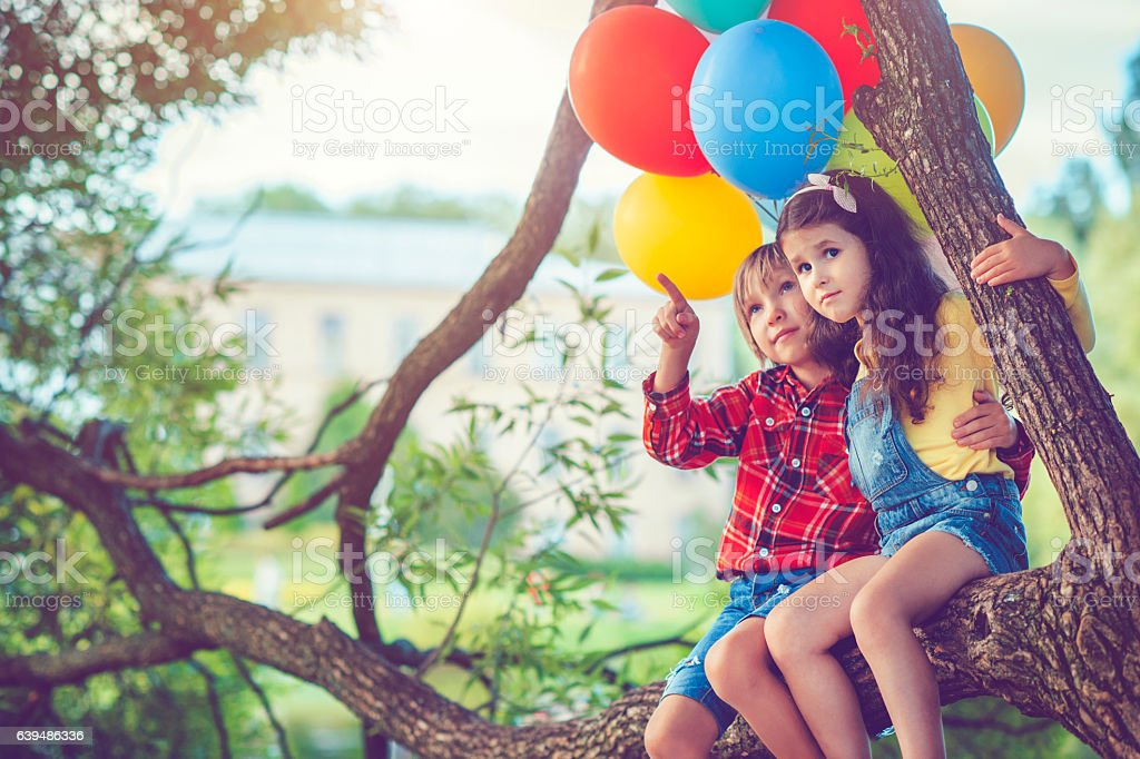 Little boy and girl with balloons stock photo