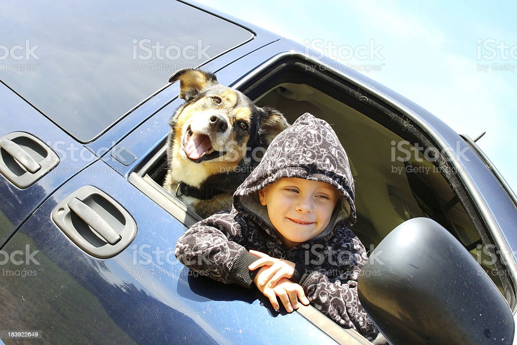 Little Boy and His Dog Hanging Out Minivan Window stock photo