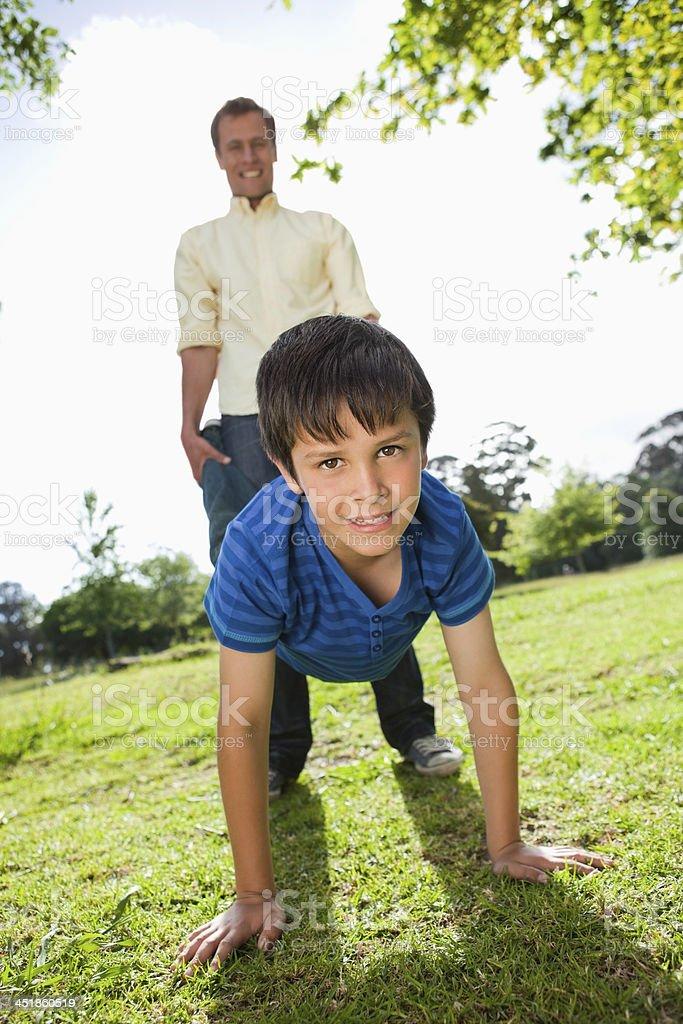 Little boy and his father having a wheelbarrow race stock photo