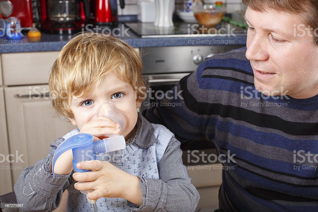 Little boy and his father making inhalation with nebuliser stock photo