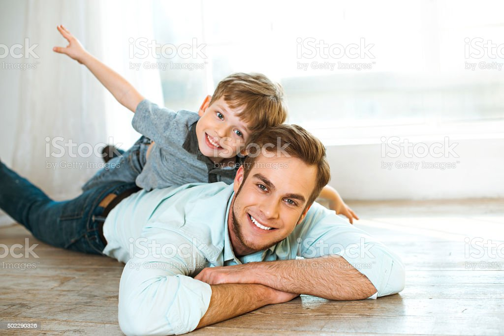 Little boy and his father on wooden floor stock photo