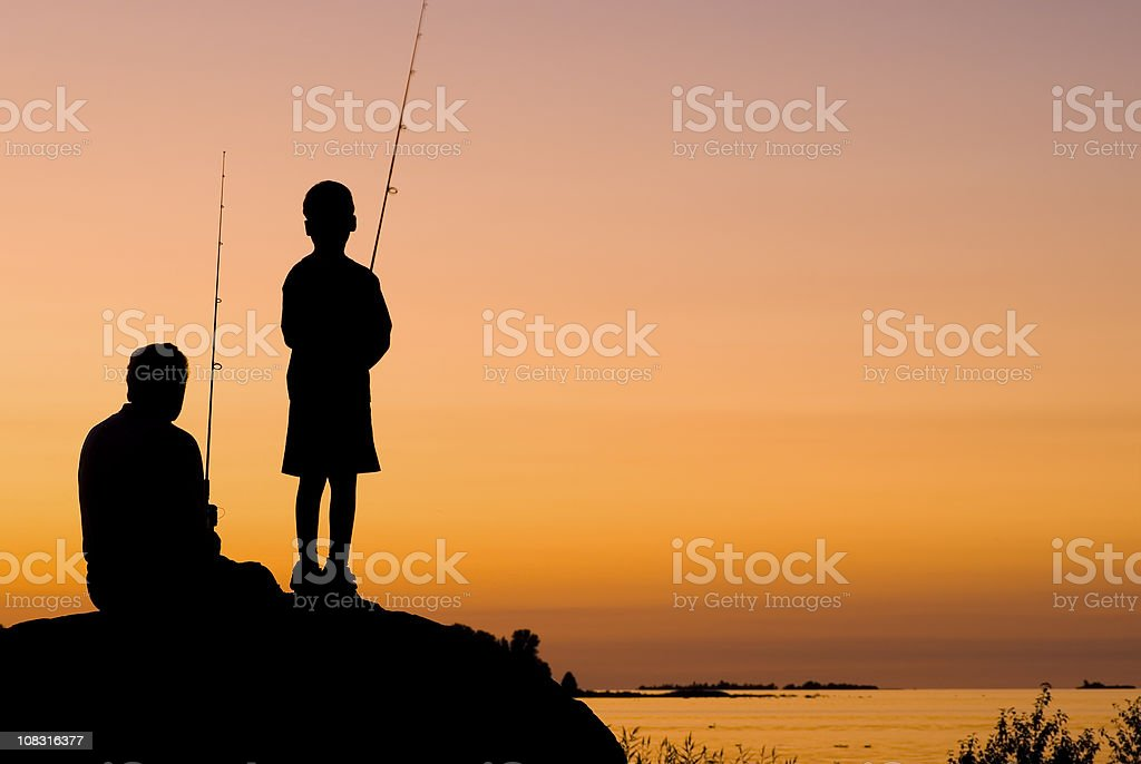 Little Boy And His Grandfather Fishing At Sunset - I stock photo