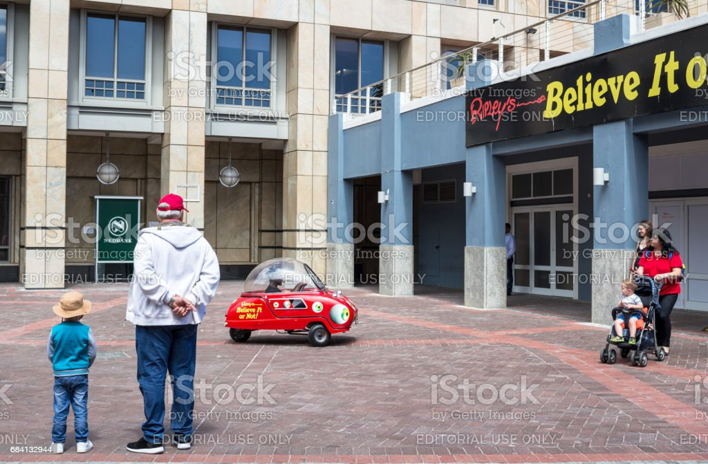 Little boy and his grandfather looking at 'Ripleys Believe it or not' Peel P-50 car, smallest road legal car in the world, at V & A Waterfront Cape Town - Illustrative editorial image stock photo