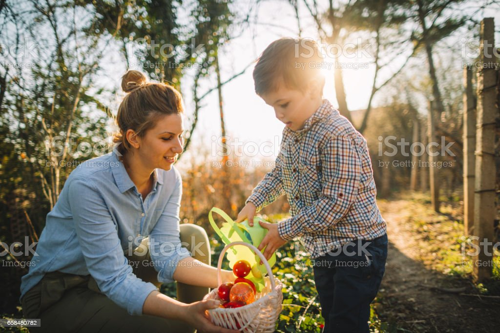 Little boy and his mom on Easter egg hunt stock photo