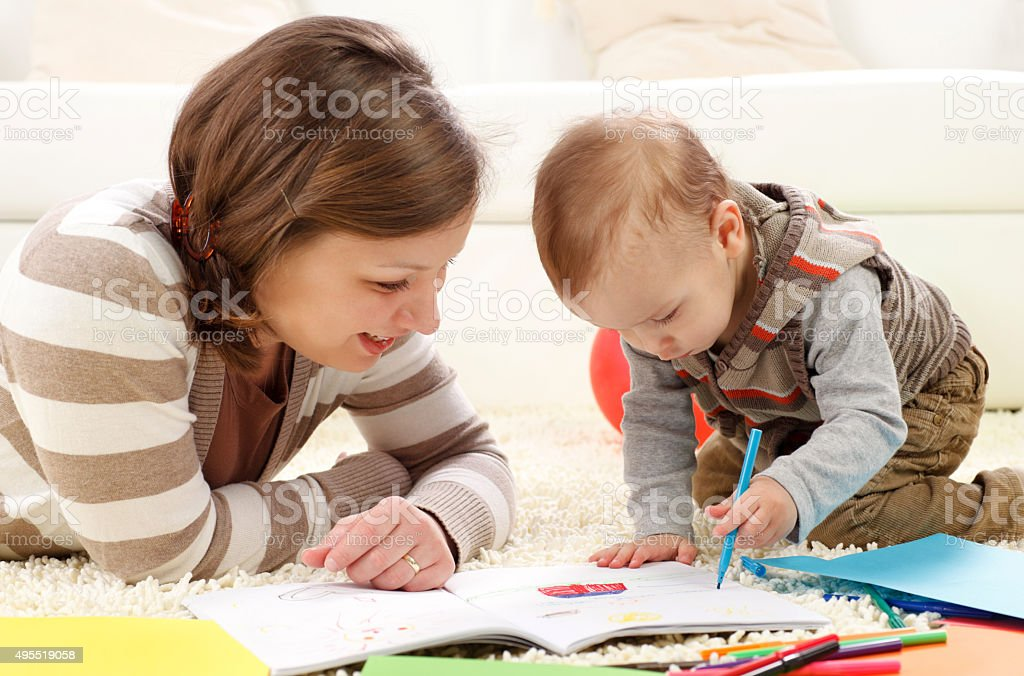 Little boy and his mother coloring at home. stock photo