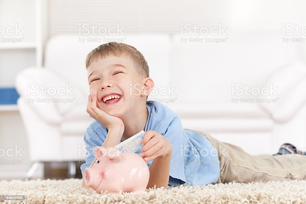 Little boy and his mother inserting money into piggy bank royalty-free stock photo